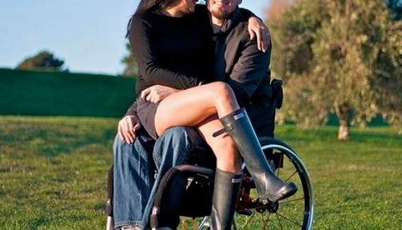 Девушка в мини юбке и сапогах сидит на коленях у инвалида в коляске в поле