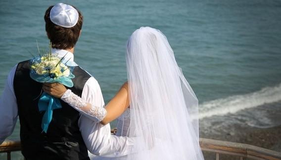 Еврейская свадьба - молодая пара в еврейской одежде на берегу моря стоит спиной