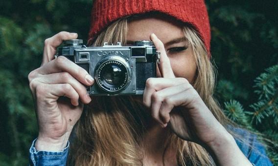 Фотография девушки в красной шапке с фотоаппаратом в руках, которая фотографирует вас