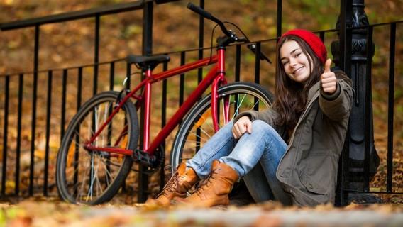 Девушка сидит на земле рядом с красным велосипедом осенью