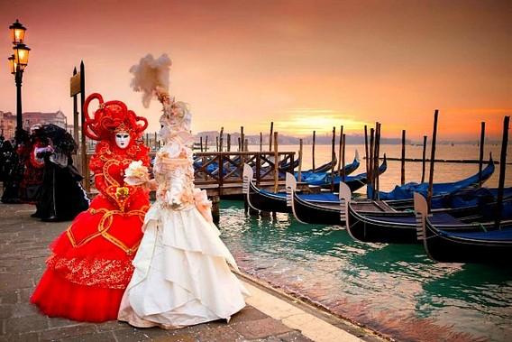 Итальянский маскарад в Венеции - две девушки в старинных платьях и масках на фоне берега с гондолами
