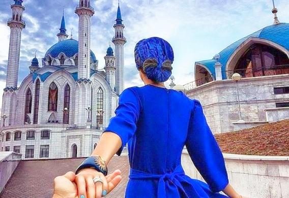 Мусульманка в синем платье и головном уборе ведет мужчину к мечети Кул Шариф в Казани