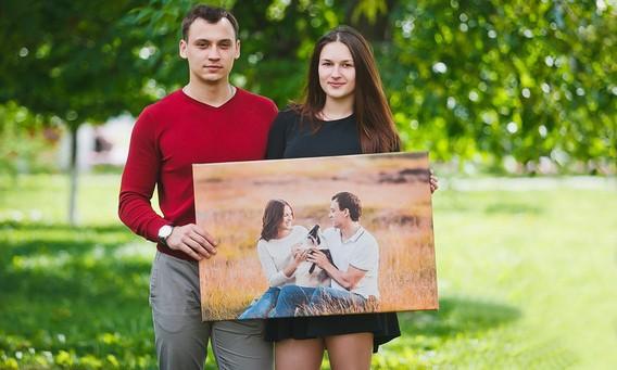 Пара стоит и держит печать на холсте общей фотографии