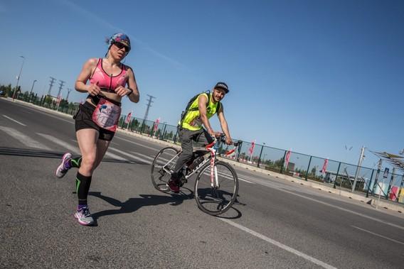Велосипедист и бегунья на соревновании бегут по асфальтовой дороге