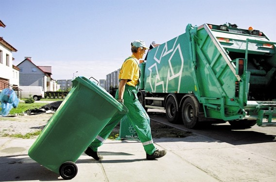 Вывоз мусора - человек ведет контейнер к авто